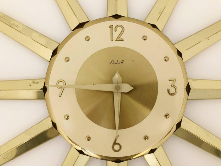 Large spike starburst clock by Roxhall. Featuring gleaming brass colored metal sunburst points with a brushed brass colored face and numbers.  The archetypal design makes this clock appropriate for a number of locations, from classic and