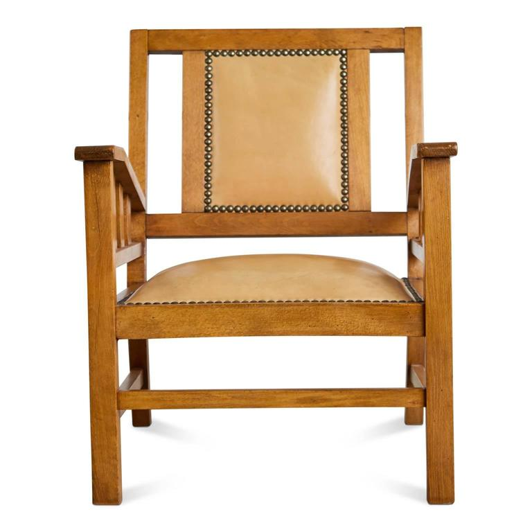 An exemplary example of Art Deco Modernist armchairs by French designer  Francis Jourdain. The simple, straightforward composition is comprised of a stained beech frame with a slanted back and pale tan color upholstery as well as being finished