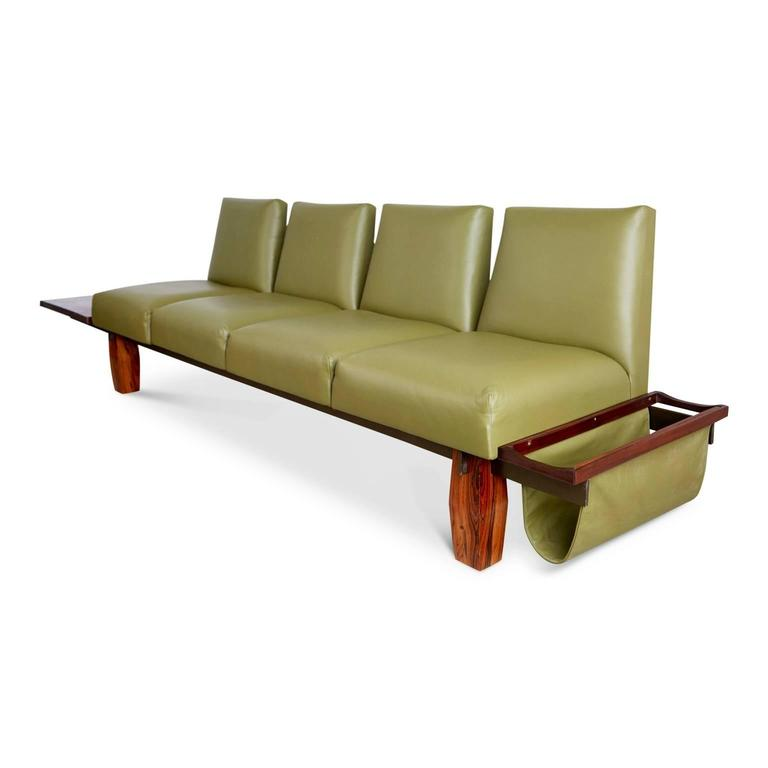 Wonderful example of one of Jorge Zalszupin's designs for the Brazilian manufacturer L'Atelier. This sofa features a Brazilian rosewood frame with a floating side table at one end and a sling magazine rack the other fabricated from the same muted