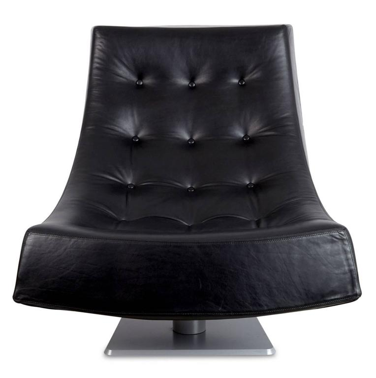 Generously proportioned tufted black leather scoop style lounge chairs. These armless chairs have a semi-swivel mechanism, perfect for diverting your conversation focus from a comfortable seated position. The gentle curve of these laid back chairs