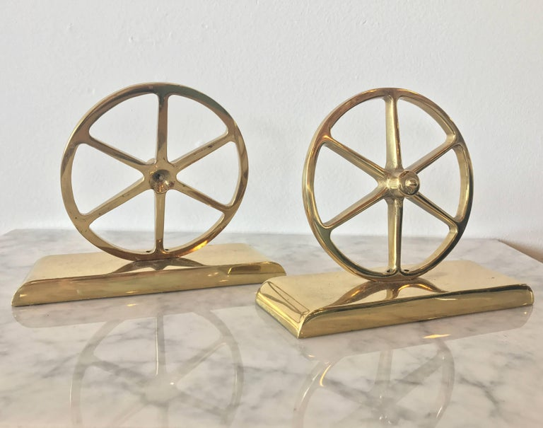 Lustrous pair of wagon wheel bookends in gleaming brass by Virginia Metalcrafters. The underneath is the stamped VM logo and are numbered.