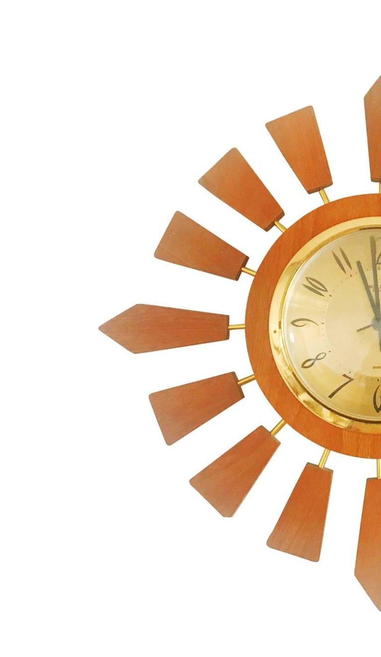 A very unique and more rare starburst clock by Anstey Wilson, England. Featuring alternating short teak wood sunbeams.  This example is a rare find as they were not mass-produced as other similar era starbust clocks like the ones from Elgin, Seth