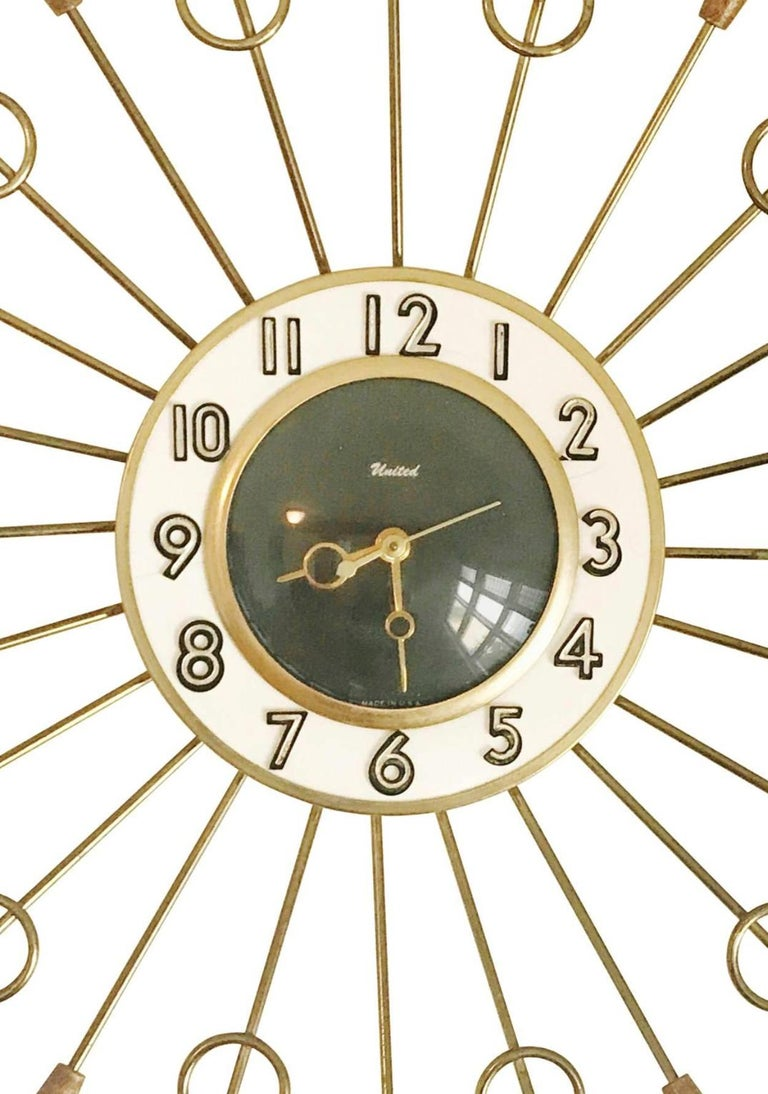Wonderful starburst clock by United. Featuring alternating teak wood ended spindles and brass rods with circular detail, creating a striking contrast.   The archetypal design makes this clock appropriate for a number of locations, from classic and
