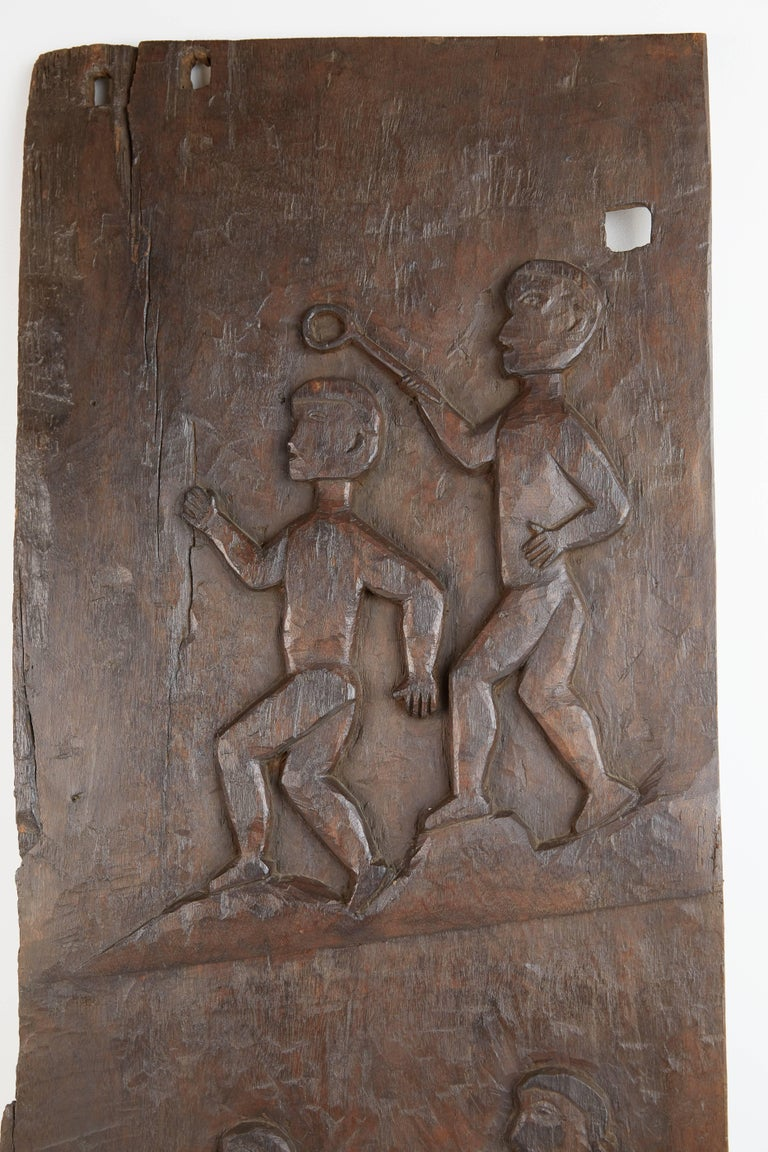 Decorative African carved large granary door featuring figures holding various tools carved in the traditional manner by tribal artisans. At one end the door can be mounted using two holes and it also has a wire affixed to the back for hanging on