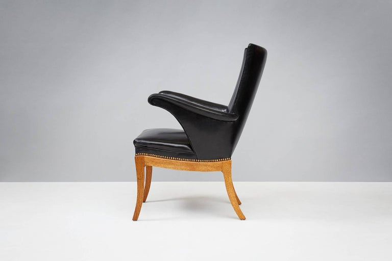 Frits Henningsen (1889 - 1965)  Pair of armchairs, 1932  Designed and produced by master cabinet maker Frits Henningsen in Denmark, circa 1932. Patinated oak base, seats upholstered in black leather and fitted with brass nails.   Henningsen,
