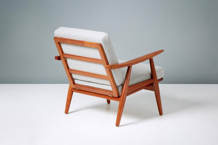 Hans Wegner GE-270 lounge chair, 1956  Classic Wegner lounge chair produced by GETAMA in Gedsted, Denmark in the 1950s. Restored teak frame with exposed brass fittings. New foam cushions covered in Svennson grey fabric.  Measures: H: 74cm  SH: