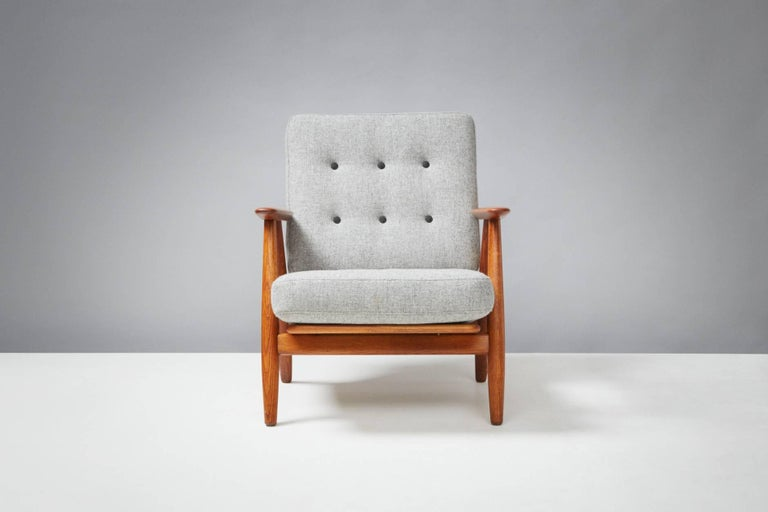 Hans J. Wegner  GE-240 'Cigar Chair, 1955  Produced by GETAMA, Gedsted, Denmark. Oak frame with teak arms. Original sprung cushions recovered in Kvadrat Hallingdal wool fabric with contrasting buttons.