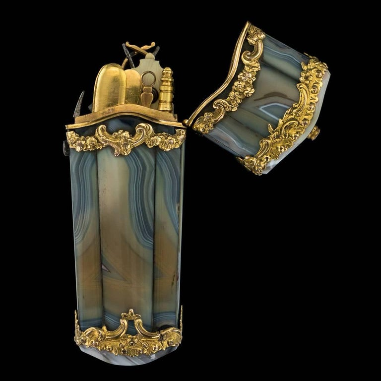 Description  Antique mid-18th Century Georgian 18-karat gold mounted on agate etui, of quiver form, the openwork gold mounts chased with scrolls and flowers, banded grey agate panels, enclosing contemporary and later gold and steel implements: fan