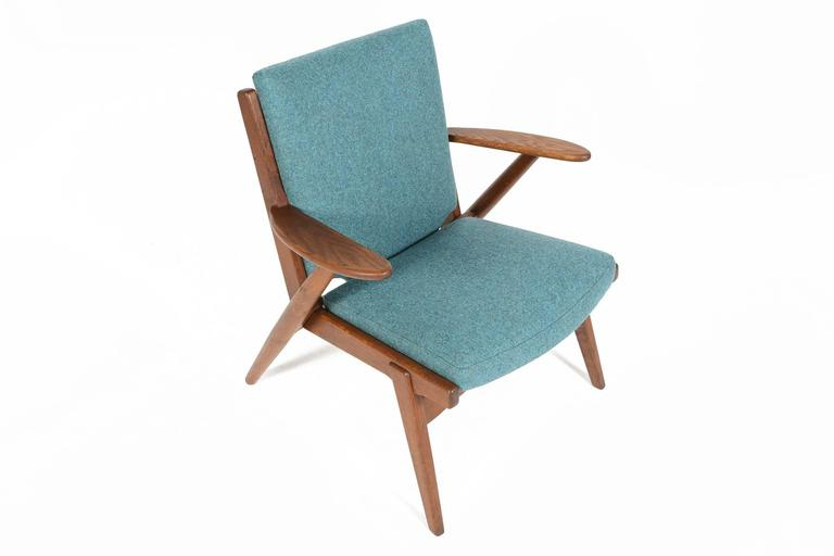 This exceptional stained oak lounge chair was designed in the style of Poul Volther and features exquisite design elements. Short, paddle arms extend into the base with solid joinery throughout. Newly upholstered in cerulean