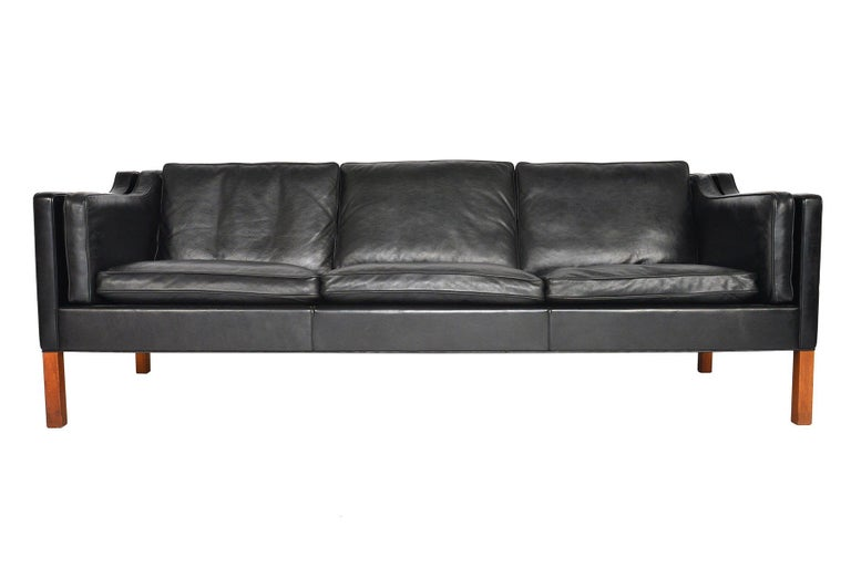 This Danish modern midcentury model 2213 three seat black leather sofa was designed by Børge Mogensen for Frederica Furniture. A staple of modern decor, this piece set a new standard for simplistic, timeless design. This completely original sofa is