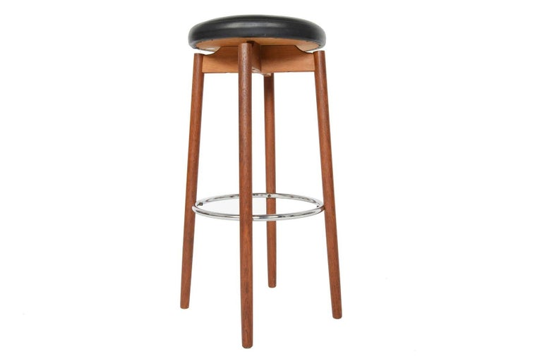 This phenomenal pair of hard to find barstools was manufactured by Hugo Frandsen in Spottrup, Denmark in the 1960s. Long, elegant teak legs are accented by a floating seat covered in original vinyl. Round chrome footrests add style and