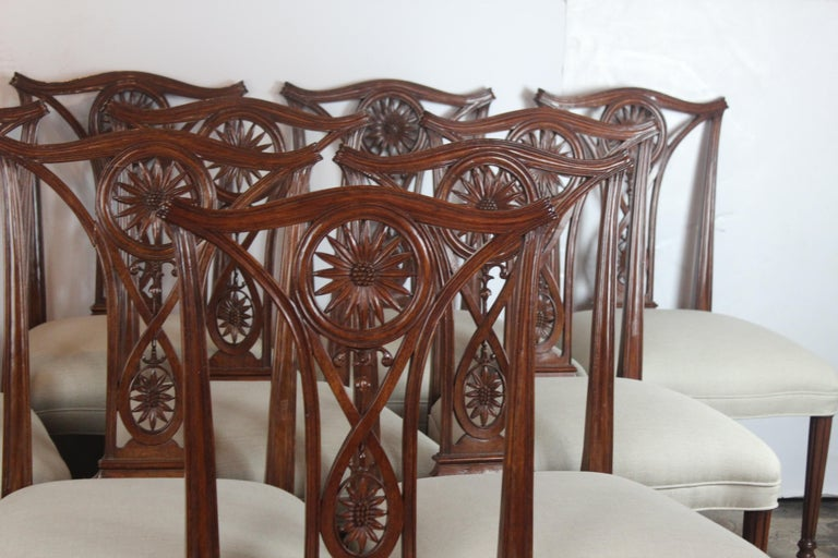 Wonderful quality set of ten dining chairs. The frame is mahogany wood carved in sunflower pattern and the legs are simple straight. The seat is covered in linen.