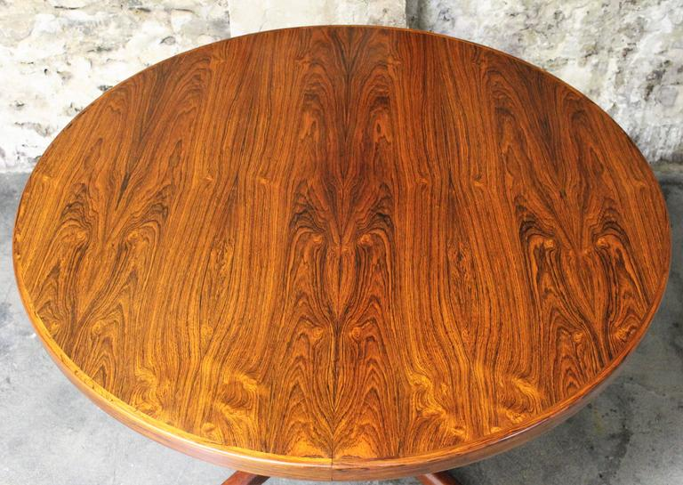A beautiful Danish Modern rosewood dining table made by Rosengaarden and designed by Erik Buch. The vibrant rosewood grain adds a level of elegance to this minimalistic table. There are two leaves that can be added to extend this table and