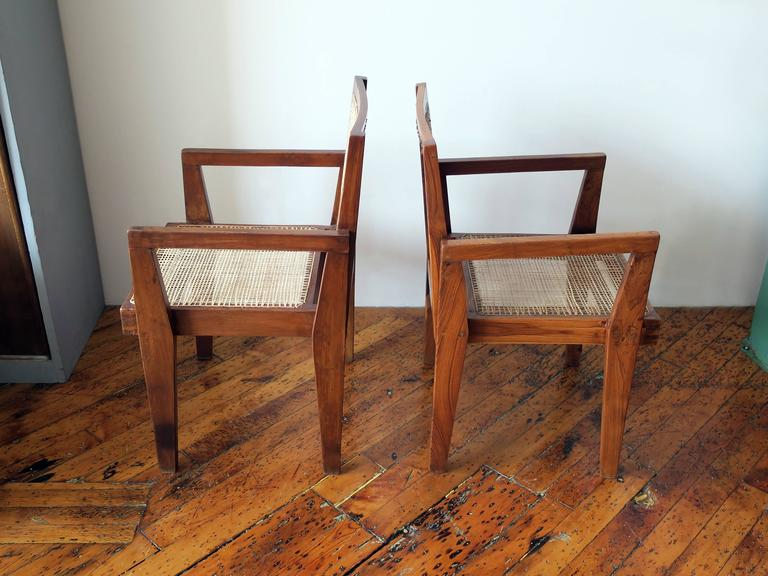 Beautiful pair of a Pierre Jeanneret clerk's armchairs from the high court, Chandigarh. Numbers present on back of chairs. Restored condition. Dimensions vary slightly due to the handmade nature of the design.