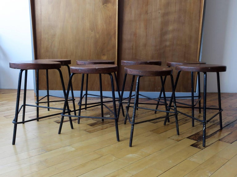 Excellent grouping of eight teak and iron low stools from the College of Architecture, Chandigarh. Set is in original condition with rich patina. A few stools show light traces of old lettering. Slight variation in seat heights due to the handmade