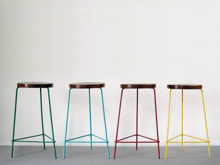Set of four stools in red, yellow, blue and green from The College of Architecture, Chandigarh by Pierre Jeanneret. Beautiful patina.