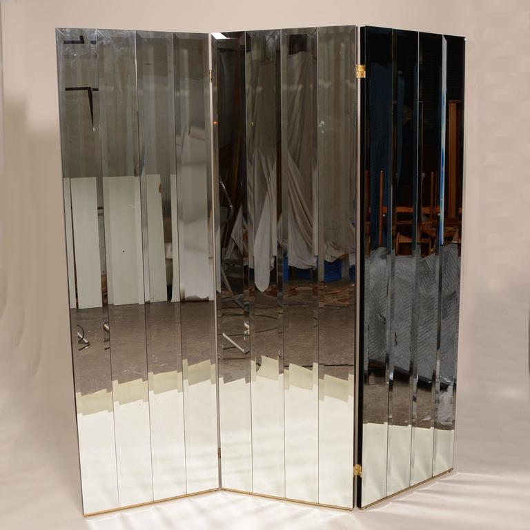 This is a rare Henredon three panel beveled mirror room divider, circa 1975. It features four separate beveled mirrors on each panel, heavy panel construction with smooth glossy black finish on the back and sides and brass base frame.