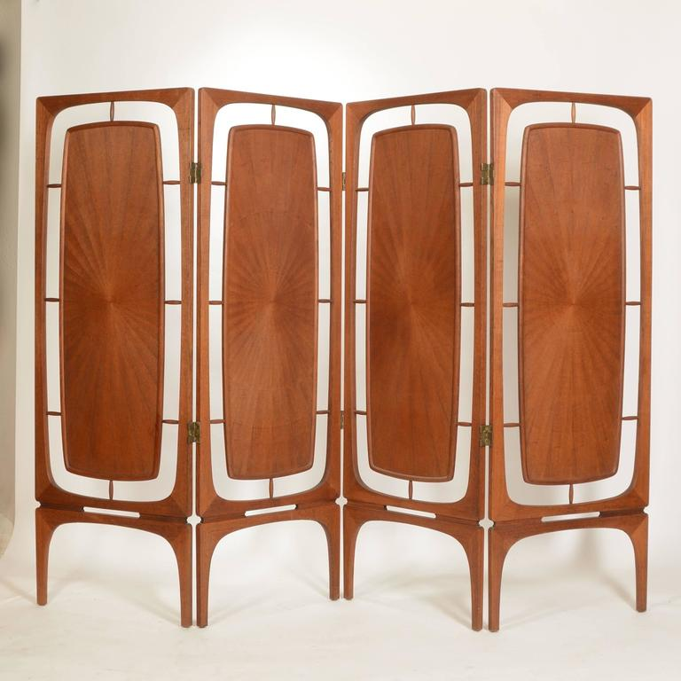 This is a beautiful and rare teak four-panel folding screen from Denmark, circa 1950.  Made from hand formed solid teak frames with radiating bookmarked veneer inserts and carved reliefs.  The condition is excellent.