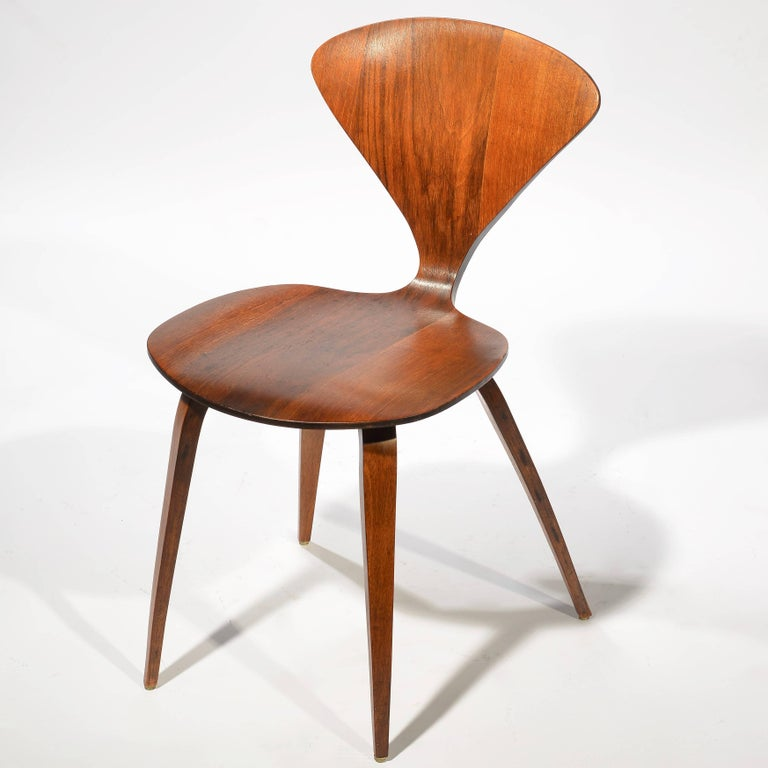 This is a rare and early set of four dining chairs in walnut plywood by Norman Cherner for Plycraft. This set retains its original finish and all chairs are in excellent vintage condition.
