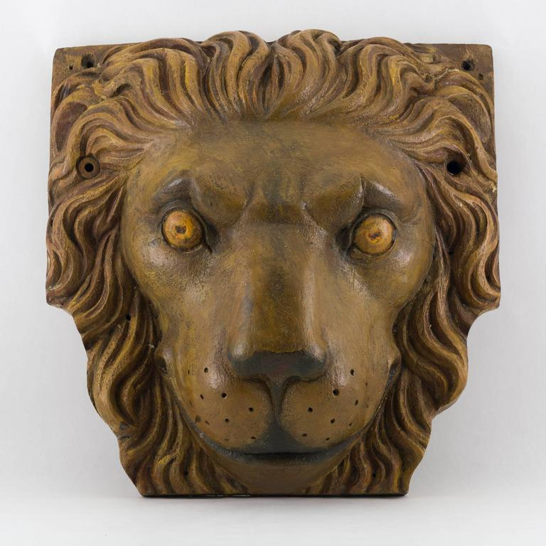 Pair of carved and painted ship's cathead terminals in the form of a lion's face. A cathead is a large beam located on either bow of a sailing ship and angled outward at about 45 degrees. The beam supports the ship's anchor when raising or lowering