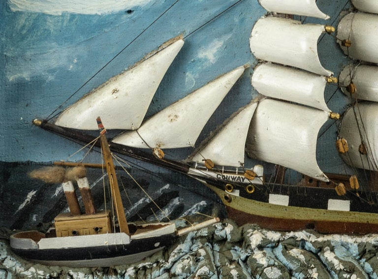 Shadow box of a three masted ship with a small steamer on a painted molded putty sea. Housed in a black paint varnished frame.