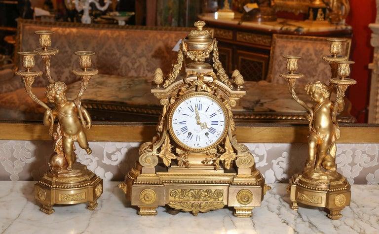 Elegant three-piece bronze doré garniture set Finely chased bronze with original gilding Fine detail work.