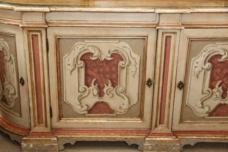 Beautiful faux marble-top finish over a conforming base with two doors flanked by two rounded doors, each carved and painted with scrolling design and supports, opens to single shelf interior. Has a key! Pale gold and deep terracotta colors grace