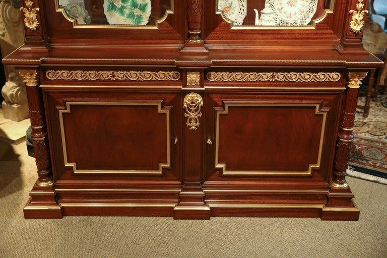 Triple breakfront rectangular cornice  above a paneled frieze of vitruvian scroll Centering a classical mask with blossoming cornucopia over a fluted Corinthian colonette flanked by beveled glazed doors opening to an adjustable Glass shelf interior