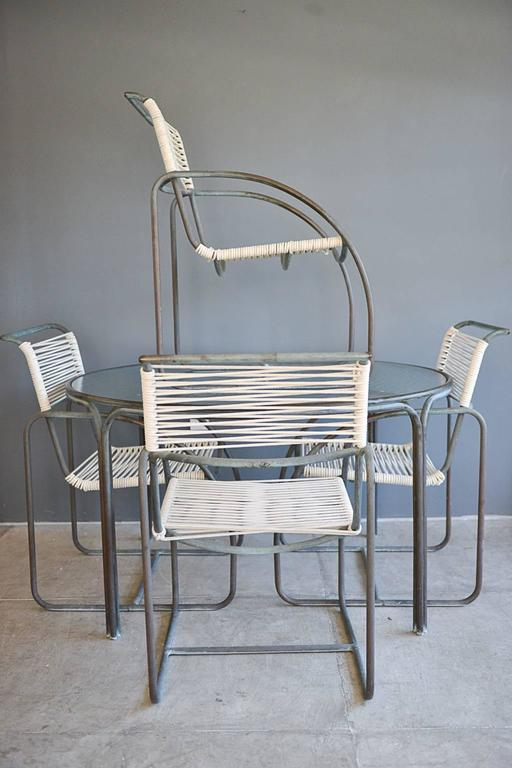 Important pair of tubular bronze and cotton cord patio dining set designed by Kipp Stewart for Terra of California. Made of tubular bronze with new cotton rope cording, these are often misattributed to Walter Lamb's work.   Table has original