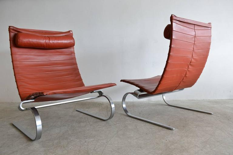 Beautiful pair of brick leather PK-20 lounge chairs by Poul Kjærholm for Fritz Hansen, circa 1989. Original brick or cognac colored leather with original neck bolsters. Marked on underside. Sculpted steel frame in excellent condition with no rust or