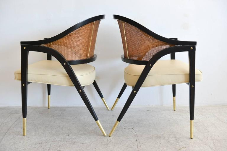 Edward Wormley for Dunbar Style 5480 pair of sculpted armchairs, circa 1955. Fully restored, ebonized frames with new ivory leather upholstery and new cane backs. Beautiful brass detailing. Rare, hard to find sold as a pair only. Showroom