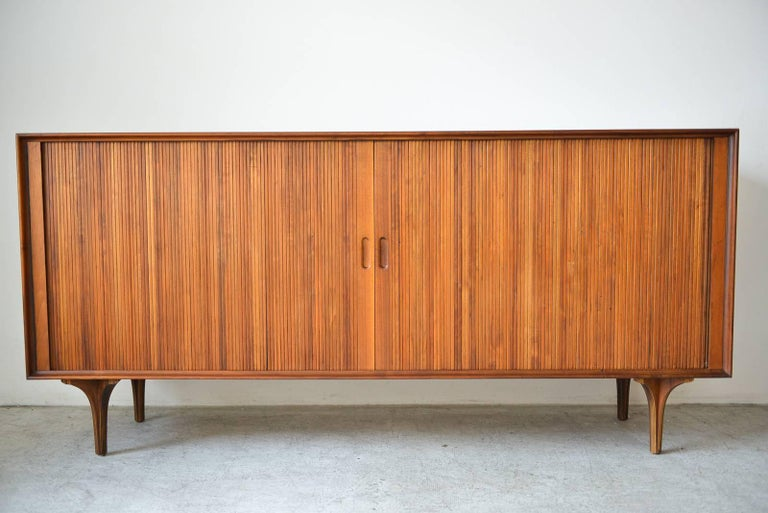 Walnut tambour door credenza by Robert Baron for Glenn of California, circa 1965. Beautiful walnut sliding tambour doors and inner adjustable shelving with vertical slots for records or media. Wood has been professionally restored and piece is in