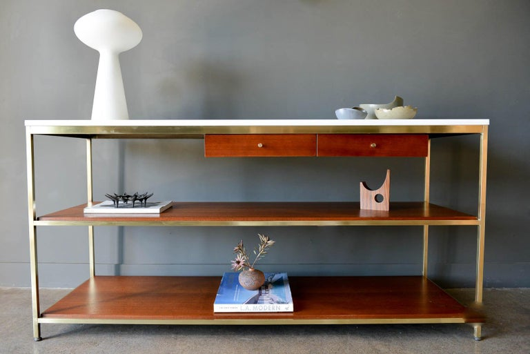 Paul McCobb brass, mahogany and vitrolite glass console table, circa 1955. From the McCobb Irwin collection, this piece features the original vitrolite glass top in excellent original condition with no chips or cracks. Brass has been polished to a