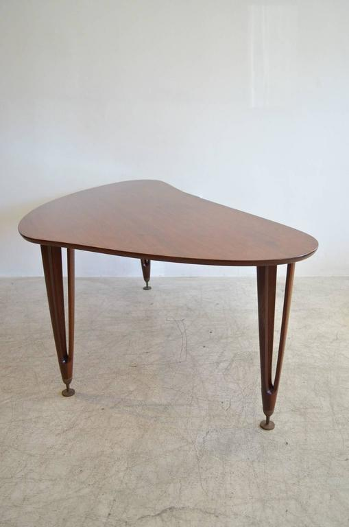Walnut boomerang coffee table with sculpted legs, tipped in adjustable brass leveling legs. Hairpin walnut sculpted tripod legs. Made by BC Mobler of Denmark.  Excellent vintage condition with hardly any wear.  Available to see in our Modern Vault
