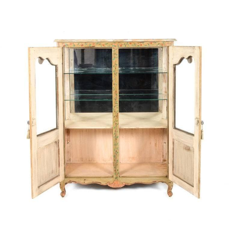 Original paint on this beautifully decorative two-door early 20th century antique French display case.