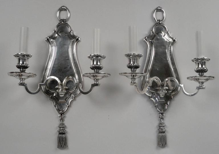This pair of silver plated sconces by Edward F. Caldwell are finely detailed, and feature tassels, and loop-form finials.