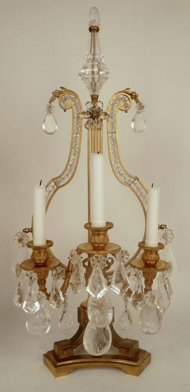 This pair of French girandoles or lustres, feature neoclassical motifs, including ram's heads and lyre form backs.
