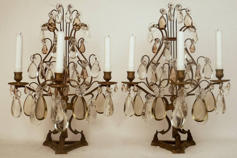 This pair of lyre form patinated bronze lustres feature clear and topaz cut crystal prisms. Originally made for candles, these candelabra may be electrified at no additional cost.