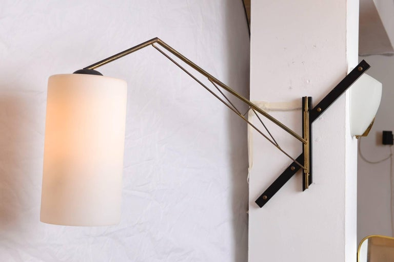 Brass and opaline shade wall light with swing arm.