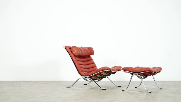Fantastic comfortable lounge chair with its footstool...  Designed by Arne Norell for Norell Möbel, Aneby Sweden 1966.  This award winning lounge chair was made of high quality flat chrome plated steel and has very thick red or orange buffalo