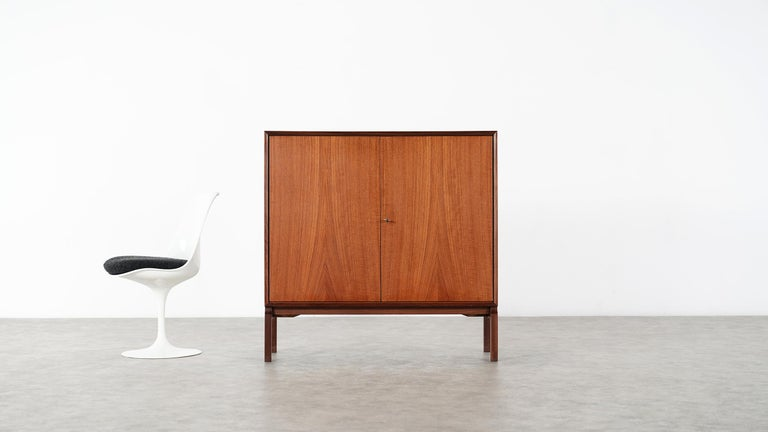 Very elegant and minimalistic teak Highboard from Denmark.  Measures: only 110cm wide, 109cm high and 40cm deep it is nevertheless spacious. 2 teakdoors closing with their original key are hiding 2 Arne Vodder like shaped drawers.  Really nice