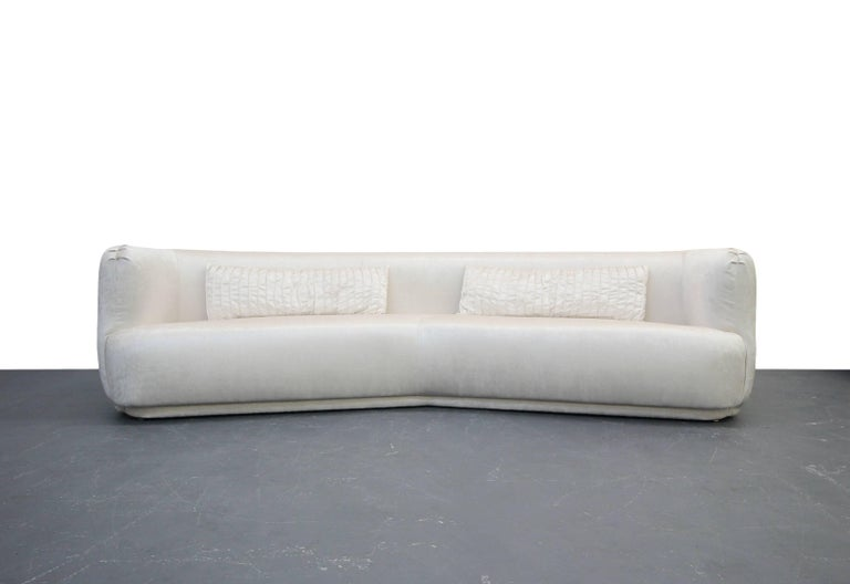 Freshly reupholstered in a beautiful cream color, high quality velvet, this beauty is dressed to impress. Angled sofas are rare, and to find one with these round edges is basically impossible. Stunning pieces, completely restored and ready for its