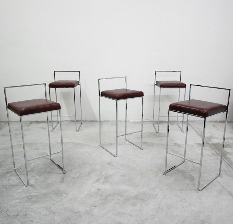 Set of five chrome, bar height stools by Milo Baughman. Stools have simple, thin, clean line chrome frames with all new butter soft maroon leather upholstery. They are in near mint condition and ready for their new home.