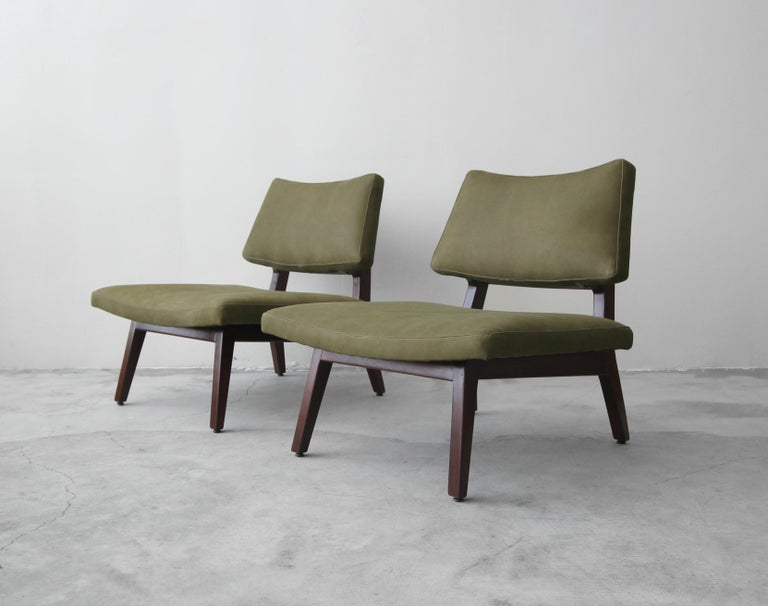 Stunning pair of sculpted side chairs by Jens Risom. A gorgeous pair of midcentury slipper style chairs with oversized seats, great curved lines and sculptural, solid walnut frames.  Professionally reupholstered in a beautiful olive green leather.