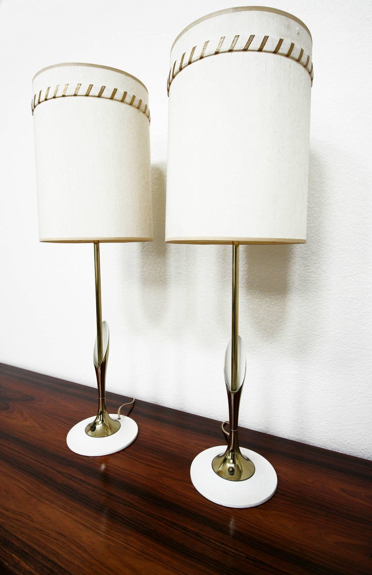 These are a super sleek and slender pair of Mid-Century Modern sculptural brass lamps by Laurel Lamp Company. They have a thin brass stem with a beautiful brass lily style detail and a unique thin white enameled base.   The lamps are pictured with
