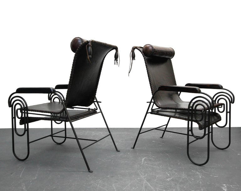 Rare pair of Art Deco style iron and leather rocking lounge chairs. Very unique, won't see another pair like them. Chairs are constructed out of aged iron, dark chocolate brown leather and wood arms with scroll and tassle details. They gently rock