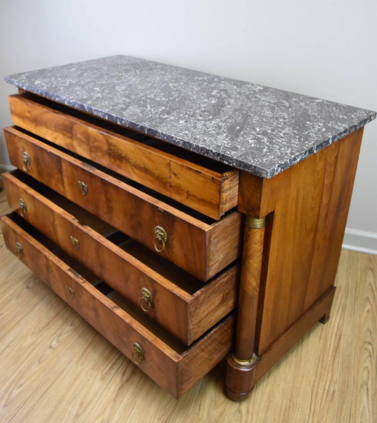 This French walnut Empire commode features a charcoal gray marble top and four functional drawers. The walnut veneer on the front is bookmatched and has a wonderful rich patina. Three of the drawers have pulls featuring a lions head motif and the