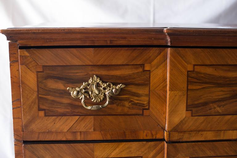 This German Baroque Commode, circa 1740, features walnut veneer with intricate intarsia on the front, sides and top. There are several places on the top where the veneer is lifting slightly but it in no way diminishes the overall beauty of this