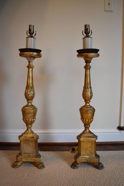 This pair of Italian candlesticks has been wired for use as lamps. The shades are parchment and ivory in color. New finials have been added as well. The lamp dimensions without the shades are as follows: Measures: 9