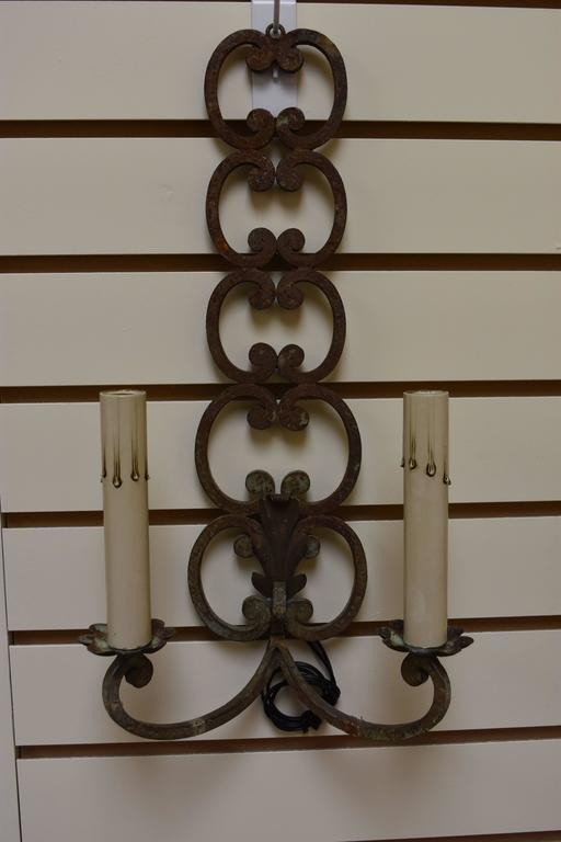 This pair of two-arm French iron sconces has been newly rewired for American use and boasts a unique scrolling design. The finish is a natural rusty / verdigris color.